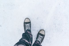 Top view of worn gray sneakers on white asphalt road Royalty Free Stock Photo