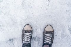 Top view of worn gray sneakers on white asphalt road Royalty Free Stock Images
