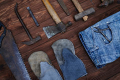 Top view of worn tools kit and denim jeans with gloves over wood Royalty Free Stock Image