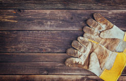 Top view of worn work gloves and assorted work tools over wooden background Stock Photos