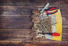 Top view of worn work gloves and assorted work tools over wooden background Royalty Free Stock Photography