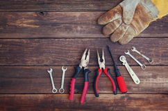 Top view of worn work gloves and assorted work tools over wooden background Stock Photo