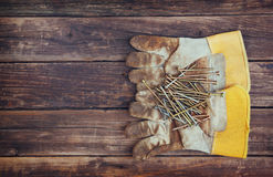 Top view of worn work gloves and assorted work tools over wooden background Stock Image