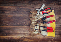 Top view of worn work gloves and assorted work tools over wooden background Royalty Free Stock Photos