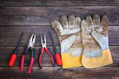 Top view of worn work gloves and assorted work tools over wooden background Royalty Free Stock Photo