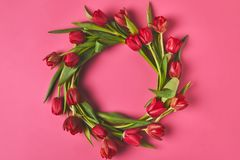 Top view of wreath made of red tulips on pink, mothers day concept stock image