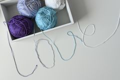 Top view of yarn balls in a wood box. Love word designed from colorful knitting wools threads. Top view of yarn balls in a wood box. Love word designed from stock image