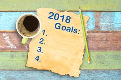 Top view 2018 year goals list on old paper and coffee cup,pencil. On office wooden table. Space for use and design Stock Photos