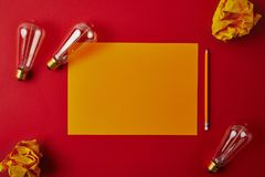 Top view of yellow blank paper with crumpled papers and incandescent lamps. On red surface stock photo