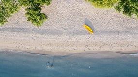 Yellow canoe and tourists on white sand beach. Top view of yellow canoe and tourists swimming on white sand beach at Flores island near Bali, Indonesia stock photos