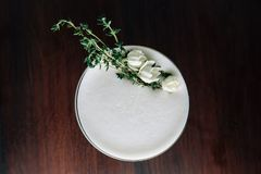 Top view of Yellow Cocktail with white foam decorated with white flower and green branch. Studio Shot.  stock photos