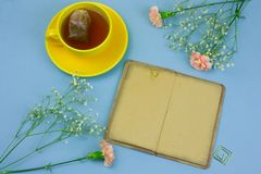 Yellow cup with tea and tea bag, vintage book and carnation flowers on a blue background spring flat lay. Top view yellow cup with tea and tea bag, vintage book royalty free stock image