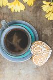 Top view of yellow flowers, blue cup of coffee and a gingerbread cookie on old wooden rustic background Royalty Free Stock Photo