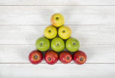 Top view of yellow, green and red apples creating a triangle shape royalty free stock photography