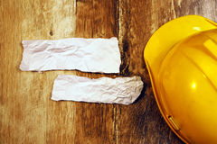 Top view of yellow hard hat and crumpled paper Royalty Free Stock Photo