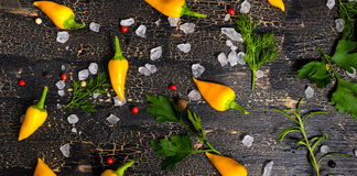 Top view of yellow hot chili peppers, sea salt, greenery on crac Royalty Free Stock Images