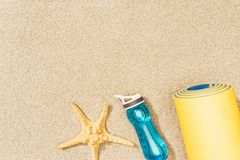 Top view of yellow mat, water bottle and sea star. On sand stock images
