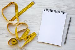 Top view, yellow measuring tape with notepad and pencil on a white wooden table. From above royalty free stock photography