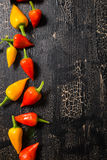 Top view of yellow and red hot chili peppers on cracks black bac Stock Photography