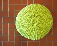 Top view of a yellow wool pouf on terracotta tiles floor. Pattern stock photos