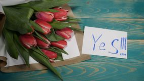 Top view of a Yes message note and Tulips flowers bouquet on a wooden table. Couple relationship concept. St Valentine s. Day. 4 k stock footage