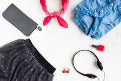 Top view of yong woman clothes and accessories. Tulle skirt, denim shirt, wallet, head phones, earrings, nail polish and kerchief. Urban style concept Stock Images