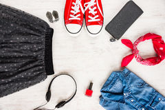 Top view of yong woman clothes and accessories. Tulle skirt, denim shirt, wallet, head phones, earrings, nail polish, sneakers and. Kerchief. Urban style Royalty Free Stock Photo