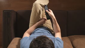 TOP VIEW: Young adult man change a TV channels by remote on a sofa at home stock video