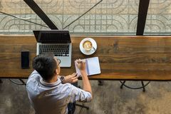 Top view of young Asian businessman writing notes royalty free stock image