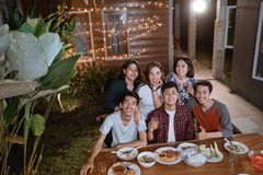 Top view of young asian people enjoy their dinner in home backyard with friend stock photography