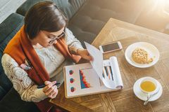 Top view. Young attractive woman, entrepreneur sits in cafe at table and working. Businesswoman is looking at charts Stock Image