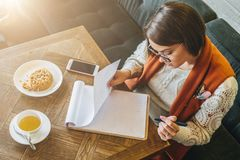 Top view. Young attractive woman sits in cafe at table and writes pen, fills out questionnaire, signs an application stock photography