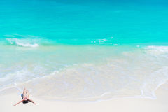 Top view of young beautiful girl lying on the beach at shallow tropical water on the seashore. Young beautiful woman on beach during tropical vacation Stock Image