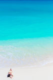 Top view of young beautiful girl lying on the beach at shallow tropical water Royalty Free Stock Photos
