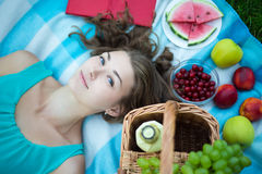 Top view of young beautiful woman with picnic basket, fruits and Royalty Free Stock Images