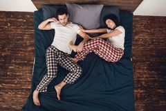 Top view. Young beautiful woman in pajama pushes adult sleeping man from bed. Top view. Young beautiful women in pajama pushes adult sleeping men from bed Stock Photography