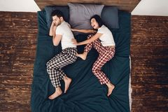 Top view. Young beautiful woman in pajama pushes adult sleeping man from bed. Top view. Young beautiful women in pajama pushes adult sleeping men from bed Stock Photos