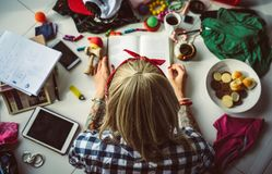 Top view of young blonde woman in a bandana read a book lying on the floor. The mess in the room. Modern student Royalty Free Stock Photos