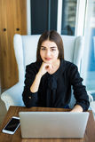 Top view, young business woman sitting at desk and working online on laptop while using smartphone. Student learning online. Top view, young business woman Stock Photography