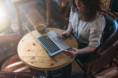 Top view, young business woman in white shirt sitting at desk and working online on laptop while using smartphone. On table cup of coffee.Student learning Royalty Free Stock Image