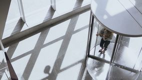 Top view on young businesswoman or female manager going to work in office through the revolving door, using smartphone. stock footage