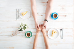 Top view of young couple holding hands and having breakfast Royalty Free Stock Image