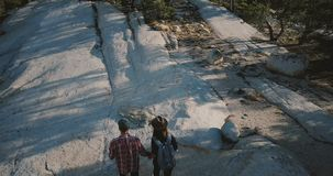 Top view young couple holding hands, hiking together on amazing white rocky mountain at Yosemite national park forest. Man and woman enjoying perfect stock footage