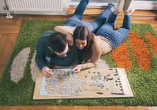 Couple having fun with puzzle royalty free stock photos