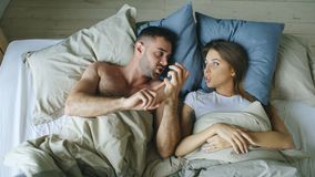 Top view of young couple lying in bed upset and argue each other royalty free stock image