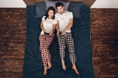 Top view. Young couple in pajamas plays by gamepads in exciting video game, lying on bed in house. Home leisure. Fun at home. Young couple spends time together royalty free stock image