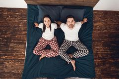 Top view. Young couple in pajamas sits on bed, legs folded together and looks up. Young couple of people are at domestic atmosphere Royalty Free Stock Images