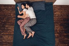 Top view. Young couple in pajamas sleeps close together on bed at home. royalty free stock photos