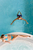 Top view - young couple relax in swimming pool. Sitting at bubble bath Royalty Free Stock Photo