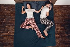 Top view. Young couple is sleeping together on big bed with blue sheet. Couple`s sleep concept. Rest at home. Sleep poses. Sleep poses for couples Royalty Free Stock Images